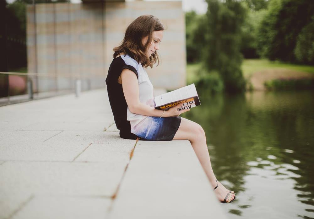 Student reading by the lake-essex